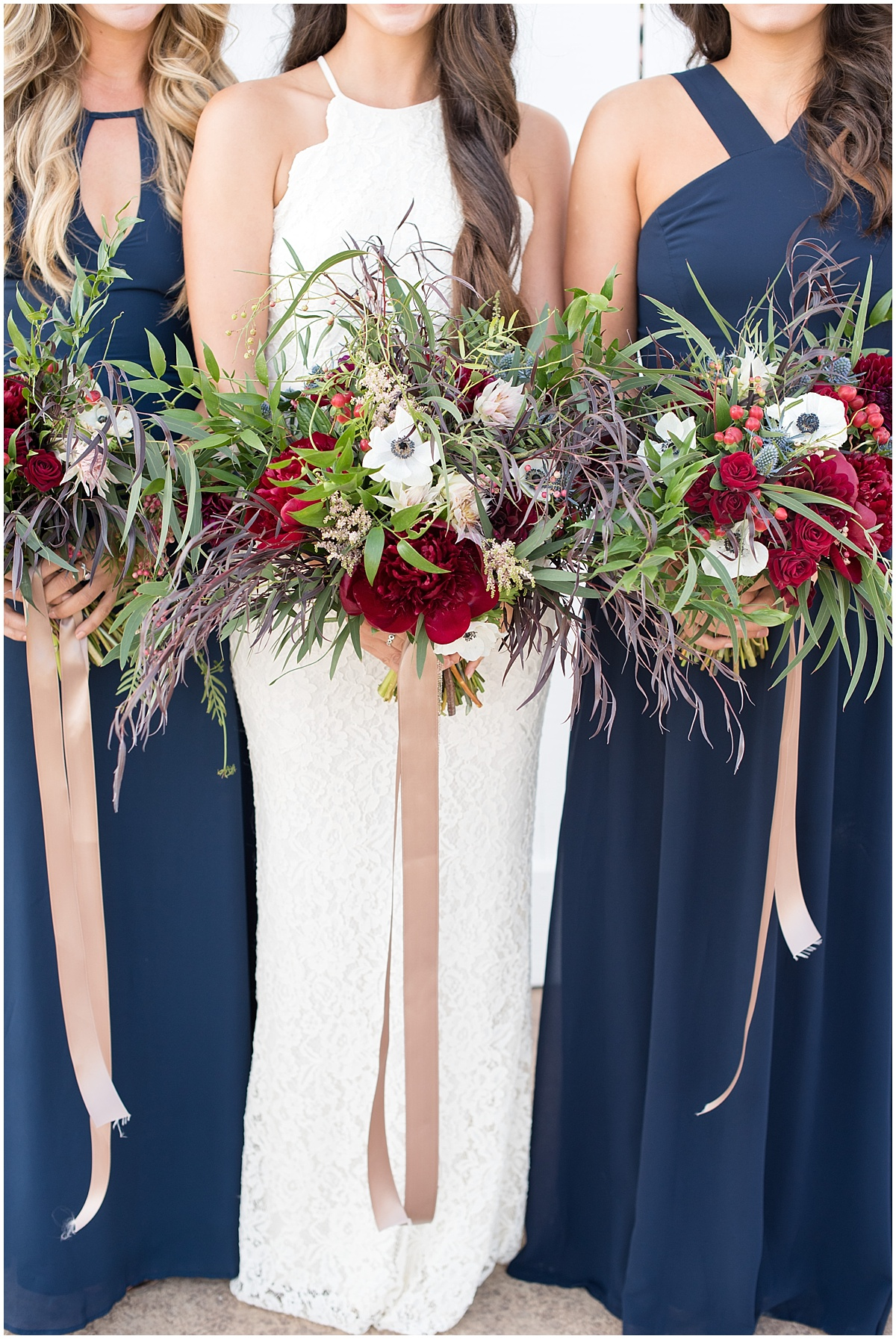 navy long bridesmaid dresses with big bouquets and ribbons. Navy and berry hues.